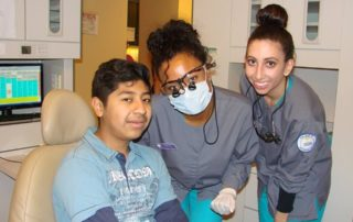 Las Vegas volunteers pose with a happy patient at Dental Care International (DCI) annual Give Kids A Smile Event in Las Vegas