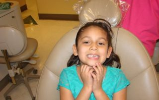 A little girl smiles after receiving free dental care at DCI annual GKAS event in Las Vegas