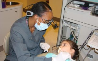 Las Vegas Pediatric Dentists working on a happy patient at Dental Care International (DCI) Annual Give Kids A Smile (GKAS) Event in Las Vegas